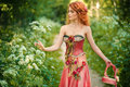 Red haired woman in a red dress collects flowers white the forest Stock Image
