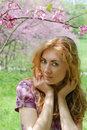 Red-haired woman under viloet flower tree Stock Photography
