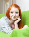 Red haired young girl relaxing on couch in livingroom room at home Royalty Free Stock Image