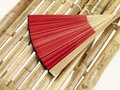 Red hand fan on bamboo bench Royalty Free Stock Photos
