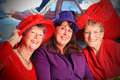 Red hat ladies three pretty smiling sitting in a cafe shallow depth of field Royalty Free Stock Photos