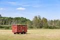 Red Hay Wagon in a Farm Field
