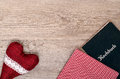 Red heart with checkered cloth and book on old wood Royalty Free Stock Photo