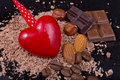 Red heart with coffee beans, chocolate, almonds and hazelnuts