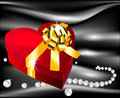 Red heart with golden bow on a background of silk black pearls decorating Royalty Free Stock Photo