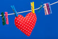 Red heart hanging on a clothesline with clothespins Royalty Free Stock Image