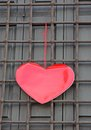Red heart hanging on the grid on Valentine's day Stock Photography