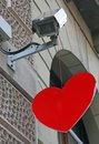 Red heart hanging from a surveillance camera of a bank Stock Image