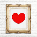Red heart icon in golden vintage photo frame on white brick wall Royalty Free Stock Photo