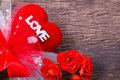 Red heart with love word and roses decorate on wooden table top Royalty Free Stock Photo
