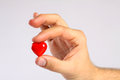 Red heart in man's fingers Royalty Free Stock Photo
