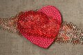 Red heart with many beads on rough fabric tie dyed paper in the shape of small transparent pearl vintage background Royalty Free Stock Photo