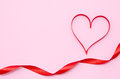 Red heart ribbon isolated on pink background Stock Photo