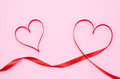 Red heart ribbon isolated on pink background Royalty Free Stock Photo