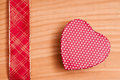Red heart and ribbon on a wooden board Stock Photos