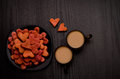 Red heart-shaped cookies and two mugs of coffee with milk on a black table. Valentine's Day Royalty Free Stock Photo