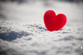 Red heart on snow Stock Photos