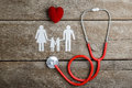 Red heart, stethoscope and paper chain family on wooden table Royalty Free Stock Photo