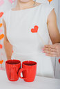 Red heart on a stick in a female hand on a white dress next to two red cups. Royalty Free Stock Photo