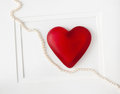 Red heart with string of pearls on white background Stock Image