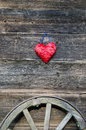 Red heart symbol on old wooden bartn wall and carriage wheel horse Stock Images