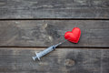 Red heart and syringe on wooden background drug addiction conc concept Royalty Free Stock Photos