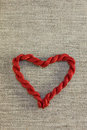 Red heart with threads made of on sackcloth background Royalty Free Stock Images