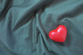 Red heart on wrinkle textile Stock Photos
