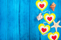 Red hearts on a colored rope and starfish blue wooden background Stock Image