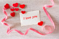 Red hearts i love you old yellowed card on whitewashed wood with many and white checkered ribbon in loops text Royalty Free Stock Photography