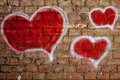 Red hearts painted on a brick wall original graffiti illustration of heart of Royalty Free Stock Photos
