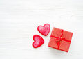 Red hearts and small gift box with a bow on a wooden white background. Royalty Free Stock Photo