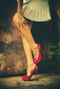Red high heel shoes woman legs in and short skirt outdoor shot against old metal door Royalty Free Stock Photography