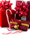 Red holiday gifts and candy canes are wrapped in paper bows highlighted with striped Stock Photos