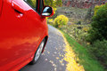 Red Honda fit driving in fall time Royalty Free Stock Photos