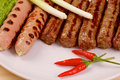 Red hot chilli peppers with grilled sausages and Royalty Free Stock Photo