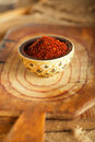 Red hot chillies pepper flakes in bowl on wooden board backgro background shallow dof Royalty Free Stock Photo