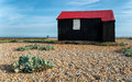 Red hut at rye in sussex a black with a tin roof on a shingle beach east Royalty Free Stock Photos