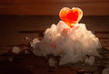 The red ice heart on a snow small group lit with the candle burn Royalty Free Stock Photo