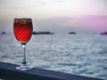 Red iced cold beverage in wine glass on wood piece with sunset background of open sea and silhouette boats Royalty Free Stock Photo