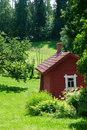 Red idyllic cottage in summer landscape Royalty Free Stock Photo