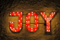 Red illuminated sign joy with the word fixed outside on a brick wall lit with bulbs and neon lights picture taken by night Royalty Free Stock Photos