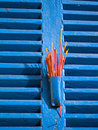 Red Incense on Blue Window Shutters Royalty Free Stock Photo