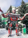 Red iron metal big strong dangerous fantastic, futuristic humanoid robot from a car with hands and head in winter