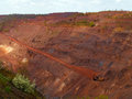 Red iron ore open-pit mine with machinery Royalty Free Stock Photo