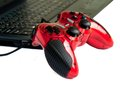 Red joystick game controller on laptop .