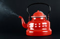 Red kettle  on black. Steam coming out. Royalty Free Stock Photo