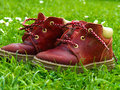 Red kid shoes kids on green grass in summer time Royalty Free Stock Photography