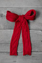 Red knitted bow for a present on grey wooden background - greeti Royalty Free Stock Photo