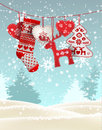 Red knitted christmas stocking with some scandinavian traditional decorations hanging in front of simple winter